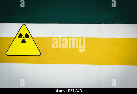 warning sign radiation caution on wall green yellow and white background - Stock Photo