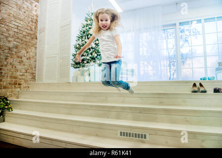 Cute girl in in casual clothes jumping from staircase - Stock Photo