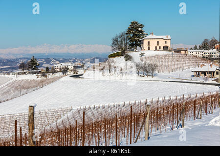 View of rural houses and vineyards on snowy hills under blue sky in Piedmont, Northern Italy. - Stock Photo