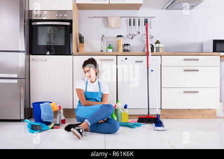 Young Woman Sitting On Kitchen Floor - Stock Photo