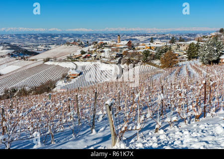 View of vineyards on snowy hills and small town of Treiso on background under blue sky in Piedmont, Northern Italy. - Stock Photo