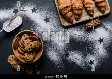 flat lay with croissants and cookies on table covered by flour with stars as big dipper constellation - Stock Photo