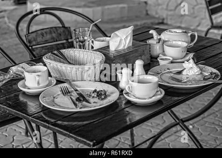 Dining table after dinner. Dirty dishes and leftover food on a table in a restaurant or cafe. Concept: eating out home. - Stock Photo
