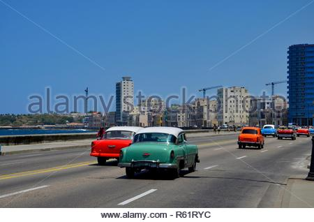 Colorful vintage cars on Malecon street in Havana, Cuba, colonial houses beside the road - Stock Photo