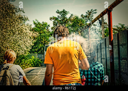 guy smokes vape and the company of young people on a walk in summer - Stock Photo