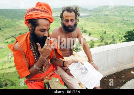 A sadhu smoke a cigarette at Trimbakeshwar, near Nasik during the Kumbh Mela 2003, Maharashtra, India. - Stock Photo
