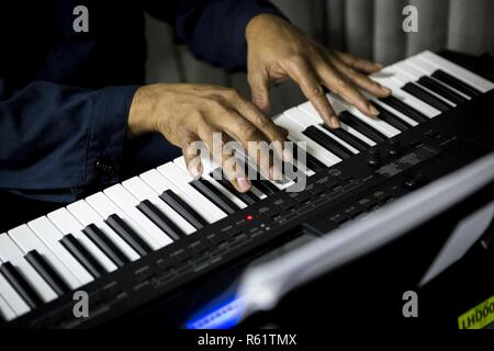 ARABIAN GULF – U.S. Navy Petty Officer 2nd Class Timothy Owens, a religious planning specialist assigned to the Essex Amphibious Ready Group (ARG), plays the piano before religious services begin aboard the Wasp-class amphibious assault ship USS Essex (LHD 2), Nov. 17, 2018. The Essex is the flagship for the Essex ARG and, with the embarked 13th Marine Expeditionary Unit, is deployed to the U.S. 5th Fleet area of operations in support of naval operations to ensure maritime stability and security in the Central Region, connecting the Mediterranean and the Pacific through the western Indian Ocea - Stock Photo