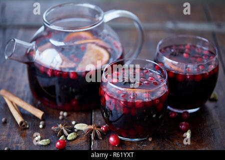 homemade mulled wine with cranberries in glasses and teapot on table in kitchen - Stock Photo