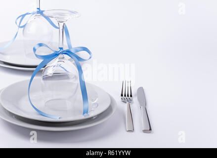 Wine glasses turned upside down with blue decoration as background for invitation and menu - Stock Photo