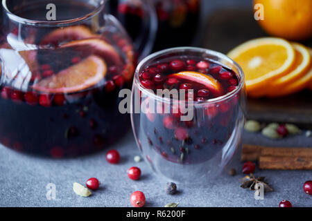 close up of homemade mulled wine with cranberries and oranges on table in kitchen - Stock Photo
