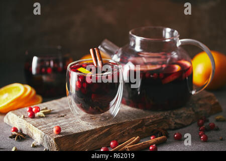 homemade mulled wine with cranberries on wooden stand in kitchen - Stock Photo