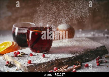 hot homemade mulled wine with cranberries with falling powdered sugar on table in kitchen - Stock Photo