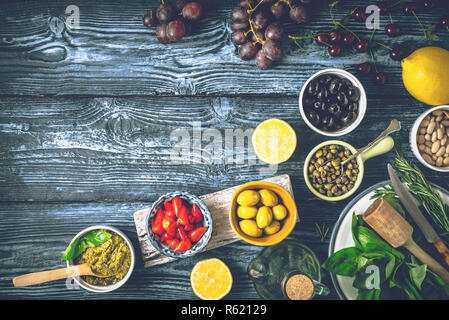 Concept of Mediterranean cuisine. Different fruit , herbs and appetizers on the blue wooden table - Stock Photo
