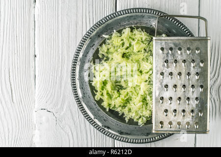 Grated cucumber in the metal plate top view - Stock Photo