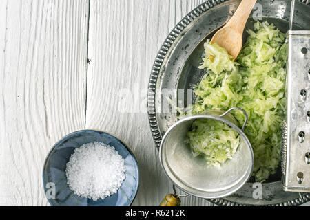 Grated cucumber with strainer and salt on the white table  top view - Stock Photo