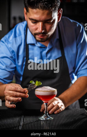 Bartender is decorating cocktail - Stock Photo