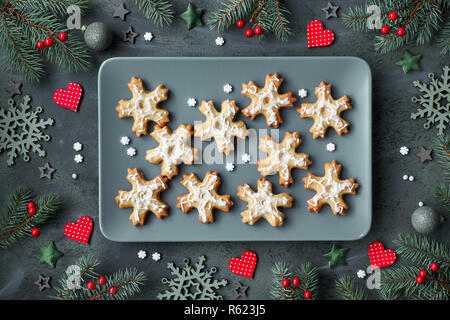 Plate of Christmas cookies shaped as snowflakes on grey plate. Flat lay on dark background decorated with Xmas tree twigs, hearts, berries and stars. - Stock Photo
