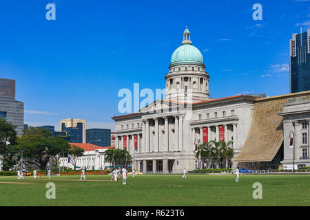 View from the Padang in Singapore towards the National Gallery Singapore (the former Supreme Court), a cricket match going on at the Padang - Stock Photo