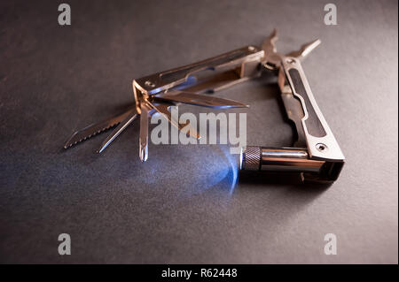 Combined pliers, multifunctional, with flashlight. Against the background of a gray texture - Stock Photo