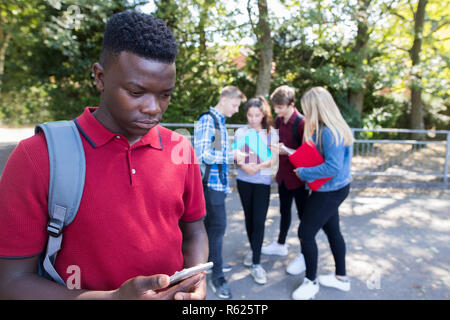 Unhappy Teenage Boy Being Bullied By Text Message At School - Stock Photo