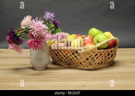 Basket with ripe apples and pears on the table stands. - Stock Photo