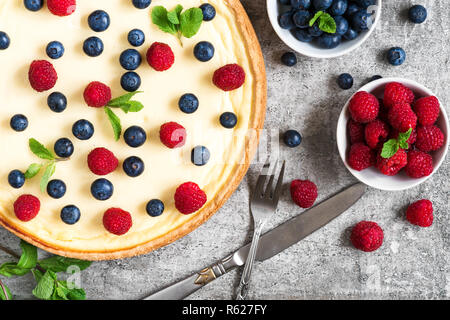 Classic New York cheesecake with fresh berries, mint and cutlery on stone background, top view. yummy breakfast - Stock Photo