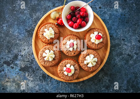 Brownie mins pies in a plate on a blue background. Festive desse - Stock Photo
