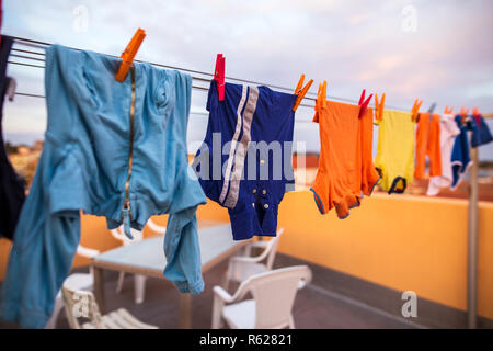 Colorful clothes hanging on rope in line - Stock Photo