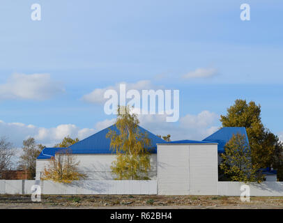 The building with siding and blue metal-plastic roof made of corrugated iron. - Stock Photo