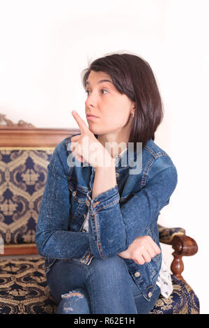 A beautiful young woman makes a quieter gesture, photo in the interior. - Stock Photo
