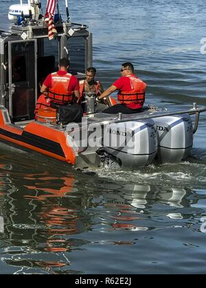 A Coast Guard 29-foot Special Purpose Craft-Shallow Water boat crew from Station Fort Myers Beach and Lee County EMS personnel are shown Tuesday, May 9, 2017 with a 28-year-old man (center) in need of medical attention aboard the SPC-SW near Estero Bay, Florida. The man was medevacked from the sailboat Anna Maria due to suffering from abdominal pain and transferred to EMS on shore in stable condition. - Stock Photo