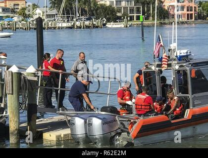 A Coast Guard 29-foot Special Purpose Craft-Shallow Water boat crew from Station Fort Myers Beach and Lee County EMS personnel aid a 28-year-old man to Station Fort Myers Beach, Florida, Tuesday, May 9, 2017. The man was medevacked from a the sailboat Anna Maria and transferred to EMS in stable condition. - Stock Photo
