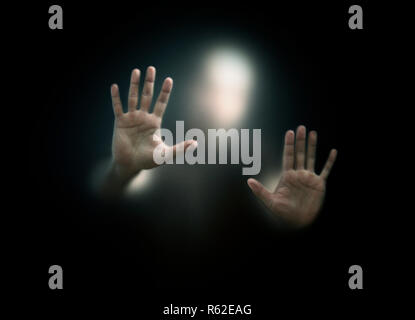 Shadowy figure behind a dusty scratched glass - Stock Photo