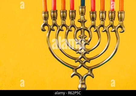 Hanukkah menorah with candles on the yellow background horizontal - Stock Photo