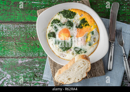 Florentine eggs with pureed spinach on the wooden table horizontal - Stock Photo