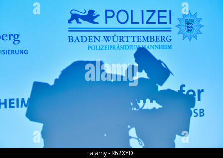 03 December 2018, Baden-Wuerttemberg, Mannheim: The silhouette of a television camera can be seen in the police headquarters on a wall on which the lettering 'Polizei Baden-Württemberg' is projected. The city of Mannheim is launching a video surveillance system that detects suspicious movements in public places at an early stage and reports them to the security authorities. Photo: Uwe Anspach/dpa - Stock Photo