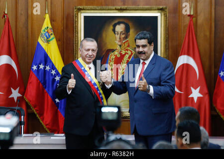 Caracas, Venezuela. 03rd Dec, 2018. The Turkish head of state Recep Tayyip Erdogan (l) is welcomed by Venezuelan President Nicolas Maduro in the presidential palace Miraflores. Recep Tayyip Erdogan is on a one-day official visit to Venezuela after attending the G20 summit in Argentina. Credit: Boris Vergara/dpa/Alamy Live News - Stock Photo