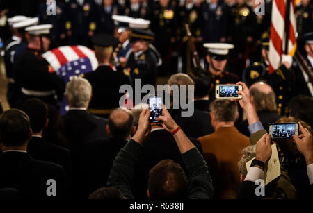 People take photos as the casket bearing the remains of former US President George H.W. Bush arrives at the US Capitol during the State Funeral in Washington, DC, December 3, 2018. - The body of the late former President George H.W. Bush travelled from Houston to Washington, where he will lie in state at the US Capitol through Wednesday morning. Bush, who died on November 30, will return to Houston for his funeral on Thursday. (Photo by Brendan SMIALOWSKI/AFP) | usage worldwide - Stock Photo