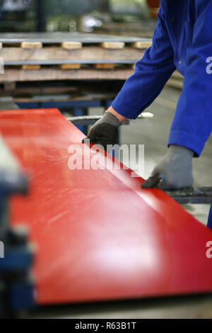 hard working, operator bending metal sheet by sheet bending machine - Stock Photo
