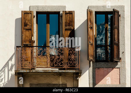 Mountain reflection in classic apartment balcony windows with open shutters - Stock Photo