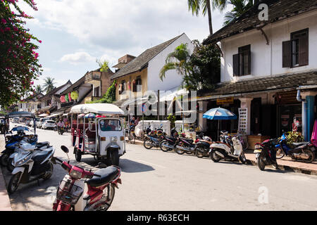 Street scene with Tuk Tuk and scooters outside shops in colonial district of old city. Sisavangvong Road, Luang Prabang, Louangphabang province, Laos Stock Photo