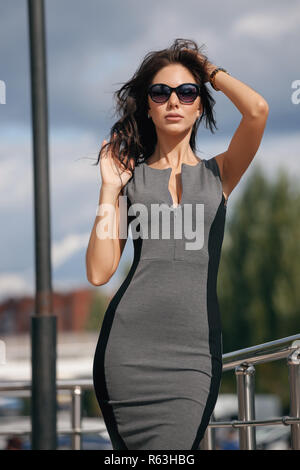 Outdoor portrait of a young beautiful fashionable happy lady wearing sunglasses, creating a city on the street. The model wears a gray dress. The girl is looking straight, her hair is developing in the wind. Women's fashion. Urban way of life - Stock Photo