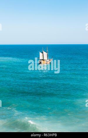 masted sailing vessel doing excursion tours off the algarve coast at benagil - Stock Photo