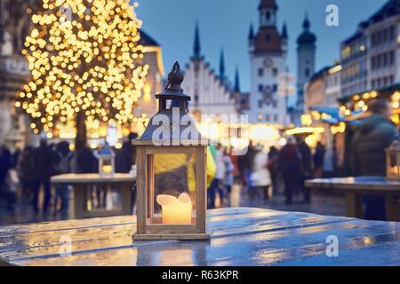 Traditional christmas market in city. Selective focus on lantern with burning candle. Marienplatz in Munich, Germany. - Stock Photo