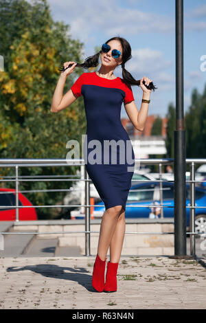 Beautiful brunette young woman in blue and red dress, wearing red high-heeled shoes, sunglasses, walking along the street. Style of fashion, shopping. The concept of women's fashion, urban lifestyle - Stock Photo