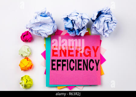 Writing text showing Energy Efficiency written on sticky note in office with screw paper balls. Business concept for Building Technology Efficiency on the white isolated background. - Stock Photo