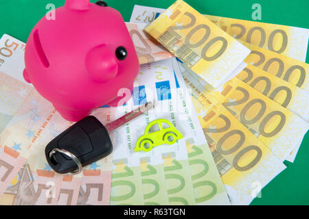 pink piggy bank with money, car key - Stock Photo