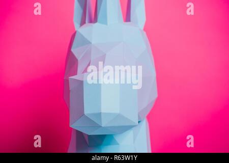 3D paper unicorn on pink background left side, horizontal. Origami toy. Origami pegasus - Stock Photo