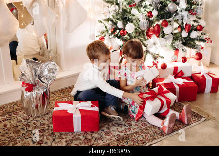 Brother in deer Christmas hat kissing his younger sister in head - Stock Photo