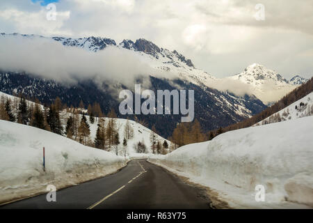 Empty twisty asphalt road stretching through deep snow towards beautiful bright white Alps steep rocky woody snowy mountain peaks under cloudy winter  - Stock Photo